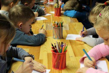 Enfants assis autour d'une grande table d'école et qui dessinent avec des crayons de couleur