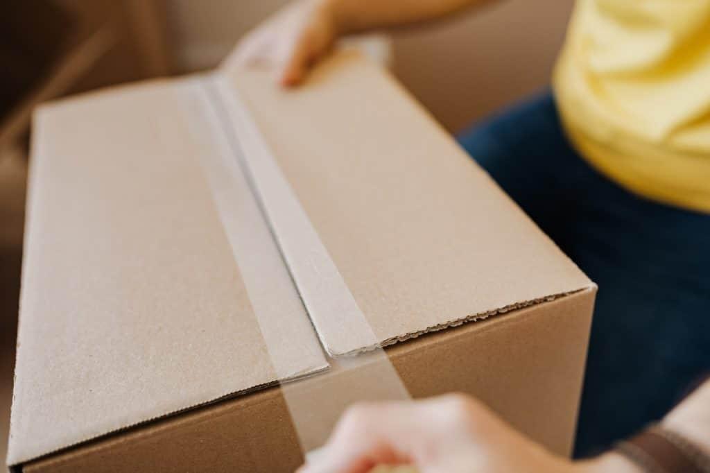 personne qu ferme un carton de déménagement